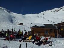 Zugspitze, Alemanha -21 fevereiro de 2012: Montanhas da neve dos cumes que relexing no sol na cabana durante o feriado do esqui e Fotografia de Stock Royalty Free