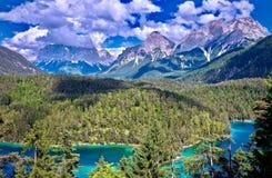 Zugspitze och dal med en cyan sjö i förgrunden i Biberwier, Tirol Royaltyfri Fotografi