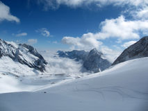 Zugspitze. Snow covered Zugspitz mountain range clouds in the valley Royalty Free Stock Photo