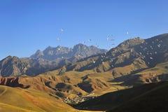 Zugvögel, die durch roten Berg fliegen Lizenzfreie Stockfotos