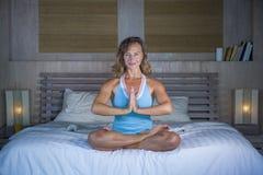 Zuhause Porträt des schönen und geeigneten gesunden übenden Yoga der Frau 30s, bei der Bettaufstellung ruhig und des entspannten  Stockbilder