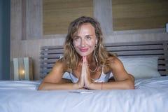 Zuhause Porträt des schönen und geeigneten gesunden übenden Yoga der Frau 30s, bei der Bettaufstellung ruhig und des entspannten  Lizenzfreie Stockfotos