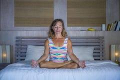 Zuhause Porträt des schönen und geeigneten gesunden übenden Yoga der Frau 30s, bei der Bettaufstellung ruhig und des entspannten  Lizenzfreies Stockfoto