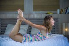 Zuhause Porträt des schönen und geeigneten gesunden übenden Yoga der Frau 30s, bei der Bettaufstellung ruhig und des entspannten  stockfotos