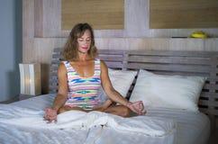 Zuhause Porträt des schönen und geeigneten gesunden übenden Yoga der Frau 30s, bei der Bettaufstellung ruhig und des entspannten  stockbild