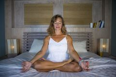 Zuhause Porträt des schönen und geeigneten gesunden übenden Yoga der Frau 30s, bei der Bettaufstellung ruhig und des entspannten  Stockfoto
