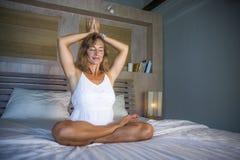 Zuhause Porträt des schönen und geeigneten gesunden übenden Yoga der Frau 30s, bei der Bettaufstellung ruhig und des entspannten  Lizenzfreies Stockbild