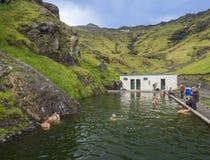 Zuid-IJsland, Seljavellir, 4 Juli, 2018: Mensen die en van groen warm water in Seljavallalaug-geheim zwemmen genieten stock fotografie