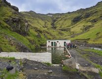 Zuid-IJsland, Seljavellir, 4 Juli, 2018: Mensen die en van groen warm water in Seljavallalaug-geheim zwemmen genieten royalty-vrije stock foto's