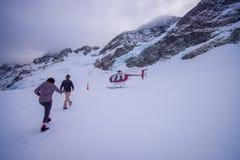 ZUIDENeiland, NIEUW ZEELAND 24 MEI, 2017: Niet geïdentificeerde mensen die aan de helikopter lopen, die over de sneeuw wachten op Royalty-vrije Stock Foto