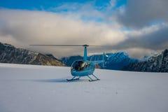 ZUIDENeiland, NIEUW ZEELAND 24 MEI, 2017: Sluit omhoog van blauwe helikopter wachtend over de sneeuw op jagers in Zuiden Westland Royalty-vrije Stock Afbeelding