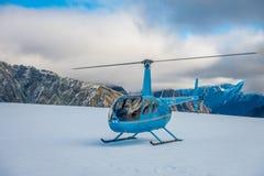 ZUIDENeiland, NIEUW ZEELAND 24 MEI, 2017: Sluit omhoog van blauwe helikopter wachtend over de sneeuw op jagers in Zuiden Westland Stock Fotografie