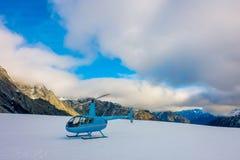 ZUIDENeiland, NIEUW ZEELAND 24 MEI, 2017: Sluit omhoog van blauwe helikopter wachtend over de sneeuw op jagers in Zuiden Westland Stock Foto's