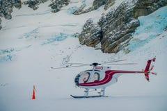 ZUIDENeiland, NIEUW ZEELAND 24 MEI, 2017: Sluit omhoog van rode helikopter wachtend over de sneeuw op jagers in Zuiden Westland Royalty-vrije Stock Fotografie