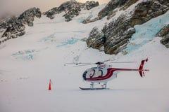 ZUIDENeiland, NIEUW ZEELAND 24 MEI, 2017: Sluit omhoog van rode helikopter wachtend over de sneeuw op jagers in Zuiden Westland Royalty-vrije Stock Afbeeldingen