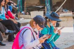 Zuidoostaziatische Buitenlandse Toeristen, Reizigers Gebruiken Mobiel in Kath stock foto