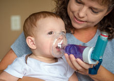 Zuigeling die ademhalingsbehandeling van moeder krijgen Stock Fotografie