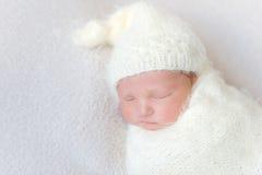 Zuigeling die een warme witte hoedenslaap, close-up dragen stock afbeeldingen