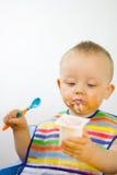 Zuigeling die Yoghurt Messily eet Stock Foto's