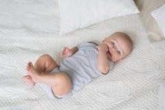 Zuigeling in een grijze babykleren op een bed royalty-vrije stock afbeelding