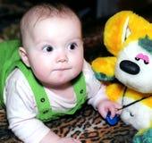 Zuigeling en haar stuk speelgoed stock foto