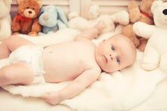 Zuigeling met blauwe ogen en nieuwsgierig gezicht op lichte deken royalty-vrije stock afbeeldingen