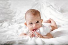 Zuigelingsbaby met grote bruine ogen die op het witte bed en likken de speciale fles liggen water met uitsteeksel Probeert om aan royalty-vrije stock foto