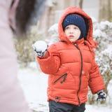 Zuigelingsjongen en moeder terwijl sneeuw Royalty-vrije Stock Afbeeldingen