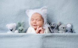Zuigelingskind in bonnet met oren die met speelgoed slapen stock afbeeldingen