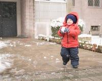 Zuigelingslooppas met een sneeuwbal in zijn handen Royalty-vrije Stock Afbeeldingen