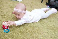 Zuigelingsmeisje in het spel van de moederclub met stuk speelgoed Stock Foto's