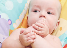 Zuigende tenen van een de kleine babyjongen op haar voeten Stock Foto's