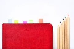 Zuivelfabriek, notitieboekje en potloden op witte bureauachtergrond royalty-vrije stock afbeelding