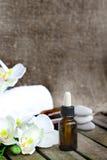 Zuivere de orchideeetherische olie van druppelbuisjeflessen close-up Stock Fotografie
