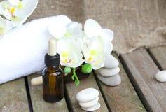 Zuivere de orchideeetherische olie van druppelbuisjeflessen close-up Stock Foto's