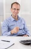 Zujubeln und glücklicher Geschäftsmann, die in seinem Büro macht winn sitzt Lizenzfreie Stockfotos