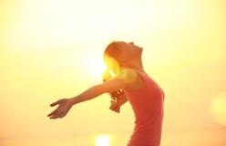 Zujubelnde Frau öffnen Arme auf Strand Stockfotos