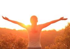 Zujubelnde Frau öffnen Arme an der Sonnenaufgangbergspitze lizenzfreies stockbild