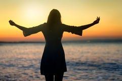 Zujubelnde Frau öffnen Arme zum Sonnenaufgang in Meer stockfotos