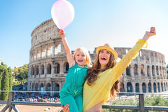 Zujubelnde Mutter und Tochter mit rosa Ballon bei Colosseum Lizenzfreies Stockfoto