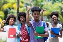 Zujubelnder afrikanischer männlicher Student mit Gruppe Afroamerikanerstudenten stockbild