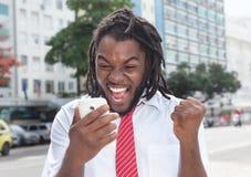 Zujubelnder Afroamerikanergeschäftsmann mit Dreadlocks und Telefon Stockbild
