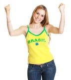 Zujubelnder brasilianischer Sportfan mit dem langen blonden Haar Stockbilder