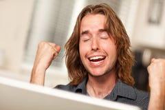 Zujubelnder junger Mann, der Laptop-Computer verwendet Stockfotos