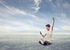 Zujubelnder junger Mann, der sein Telefon betrachtet Lizenzfreie Stockfotografie