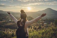 Zujubelnder Reisender der jungen Frau, der Sonnenaufgang betrachtet lizenzfreie stockfotos