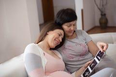 Zukünftige Großmutter, die mit Tochter genießt lizenzfreies stockfoto