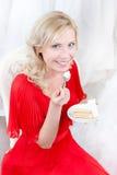 Zukünftige Braut isst den Hochzeitskuchen Lizenzfreie Stockfotos
