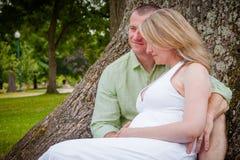 Zukünftige Eltern zusammen im Park lizenzfreies stockfoto