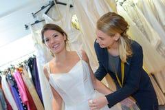 Zukünftige Frau, die auf Hochzeitskleid an der Kleiderinstallation versucht Lizenzfreie Stockfotos